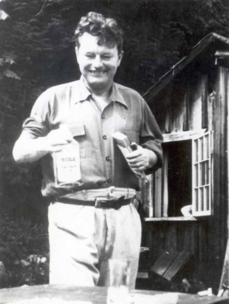 Malcolm Lowry with two of his best friends, a bottle and a book